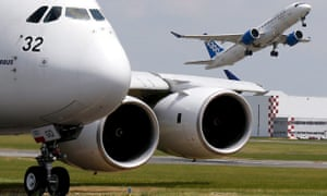 A Bombardier CS300 aicraft takes off as an Airbus A380 waits on the taxiway during an air show.