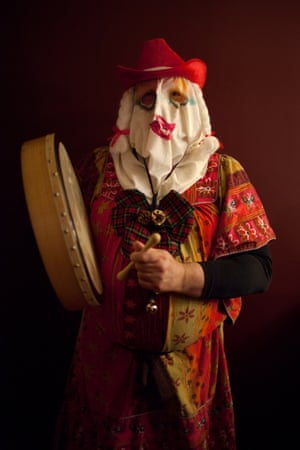 Medium shot of a mummerer in party dress, wearing a cloth mask and a red stetson hat and holding an Irish handheld drum. Mummering, St John's, Newfoundland. The hosts of these mummers parties usually serve up refreshments – Christmas cake and a glass of syrup or blueberry wine.