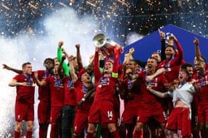 Jordan Henderson of Liverpool lifts the trophy in celebration.
