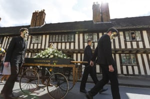 A bier carrying a flower-adorned mock coffin marking Shakespeare's death is wheeled through Stratford during the parade