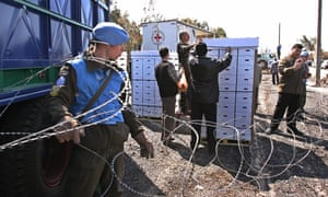 Syrian officials inspect boxes of apples from the Red Cross at the Syrian-Israeli border.