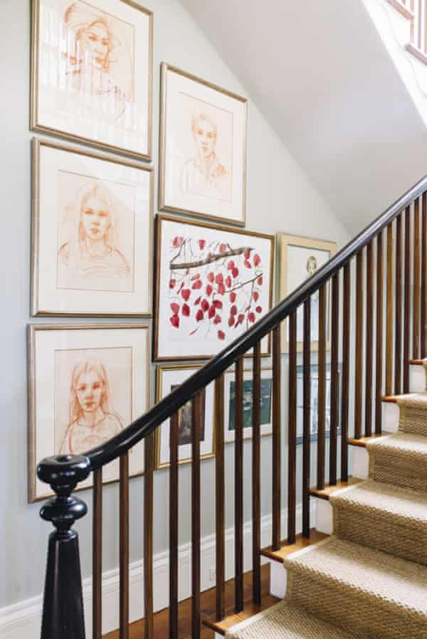 A gallery wall of family portraits along a stairway wall