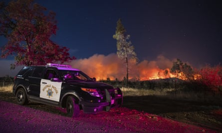 A California Highway Patrol officer watches flames that are visible from the Zogg fire near Igo, California.