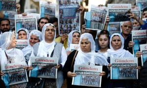 Protesters hold up copies of the Turkish daily Özgür Gündem