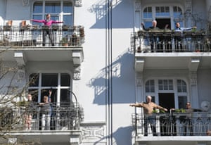 Hamburg, Germany Residents exercising on their balconies follow the instructions a fitness trainer