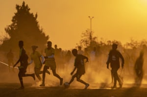 Soweto, South AfricaFootball players play a friendly match on a dusty soccer field