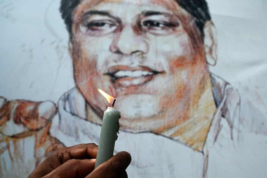A Sri Lankan journalist lights a candle in front of the grave of the murdered editor, Lasantha Wickrematunge, in Colombo on 8 January 2020, on the 11th anniversary of his death.