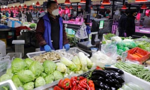A Chinese vendor sorts vegetables at a market in Beijing, China, 10 February 2020.