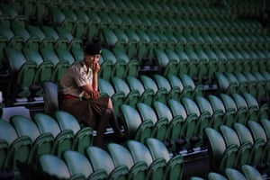 A member of the armed forces waits before play begins at the Wimbledon Tennis Championships in London, England