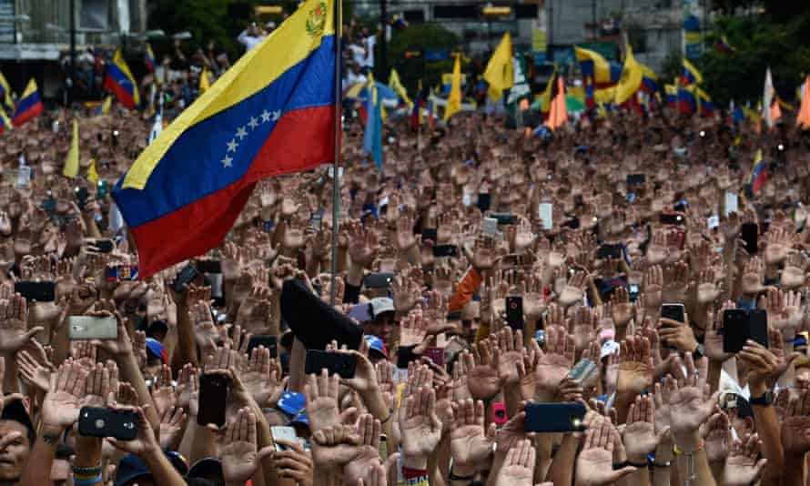 Guaidó supporters raise their hands at a rally in Caracas