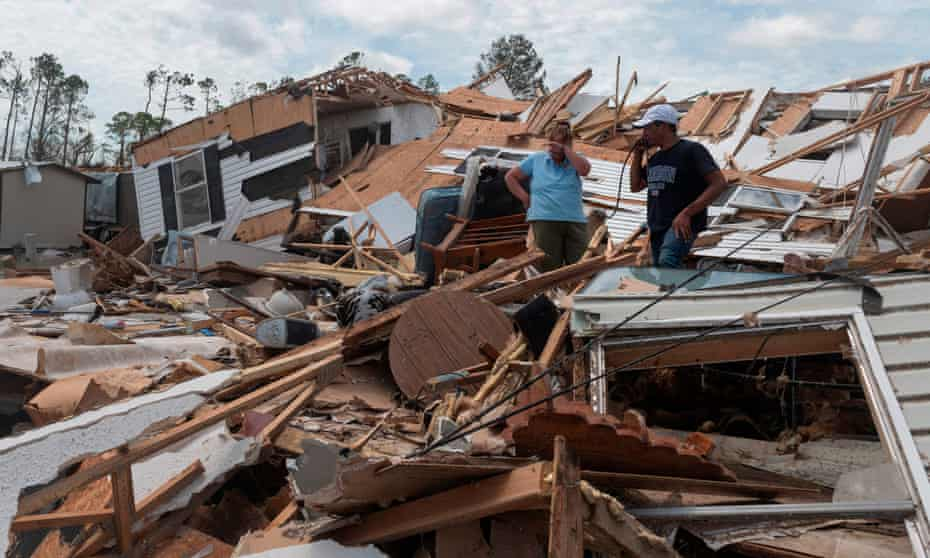 A couple react as they go through their destroyed mobile home following the passing of hurricane Laura in Lake Charles, Louisiana.