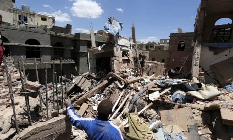 Yemenis stand over the rubble of houses destroyed by a Saudi-led airstrike on Sana'a, Yemen, in September 2015.