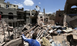 Yemenis stand over houses in Sana'a hit by an airstrike carried out by the Saudi-led coalition.