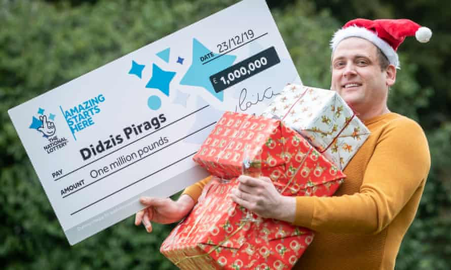 Didzis Pirags holding giant cheque and presents