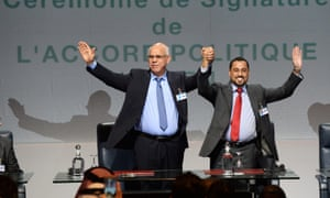 Mohammed Chouaib, of the Tobruk government, left, and Saleh Almkhozom, of the Libyan General National Congress, celebrate after signing the UN-sponsored deal.