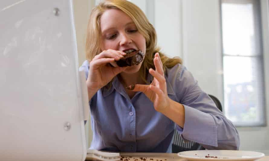 Office worker eating chocolate cake at her desk