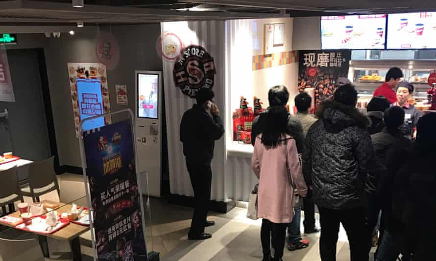 The facial recognition machine to the left sits unused as customers queue to be served by humans instead