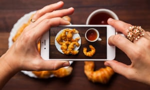 Taking a photograph with cell phone of breakfast made of one cup of black tea and six croissants.