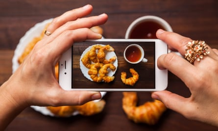 Someone photographing their coffee and croissants