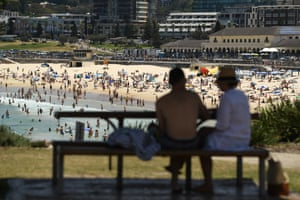 A couple sit in the shade as people flock to Sydney's Bondi Beach on Saturday to escape the sweltering temperature