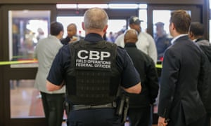 A Customs and Border Protection federal officer watches from inside the terminal during a protest at Hartsfield-Jackson Atlanta international airport, where Mohammed Tawfeeq was detained.