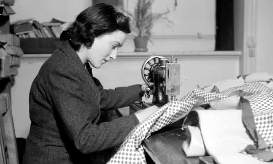 A woman using a sewing machine circa 1940.