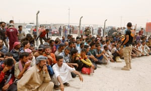 Displaced people wait for security checks from tribal fighters at a camp near Falluja