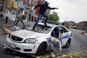 Demonstrators jump on damaged Baltimore police vehicle
