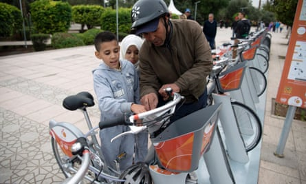 A man and his children inspect the recently installed 'Medina Bike' scheme in Marrakech, launched to coincide with the COP22 UN climate talks.