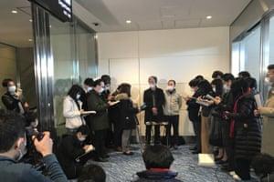 Takeo Aoyama, center left, and Takayuki Kato, center right, speak to media after landing in Tokyo