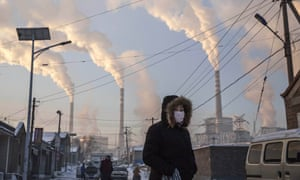 Figure in a face mask with factory chimneys in the background