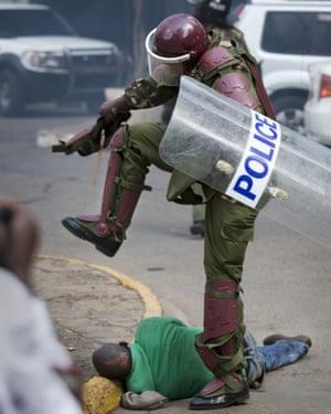 A Kenyan riot policeman repeatedly kicks a protester