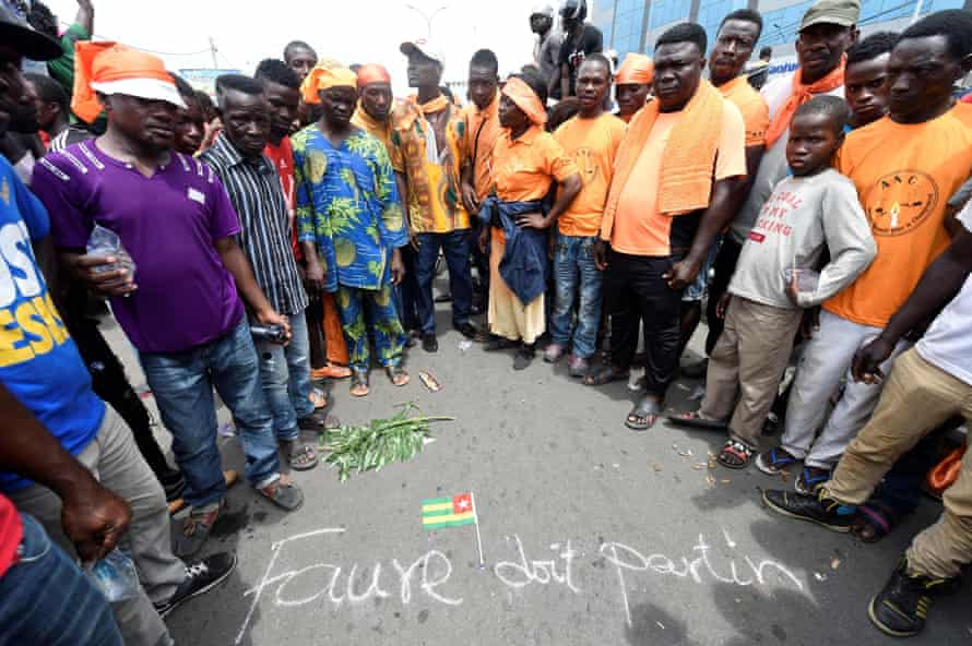 Anti-government protesters in Lomé gather around a scrawled message saying: 'Faure should leave'