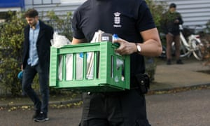 Police officer carries items in crate