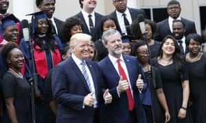 President Trump poses with Liberty University president Jerry Falwell Jr., center right, in front of a choir during commencement ceremonies at the school in Lynchburg, Va., Saturday, May 13, 2017.