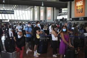 People queue in line to check-in for a British Airways flight to Heathrow airport at Nice airport on Friday.