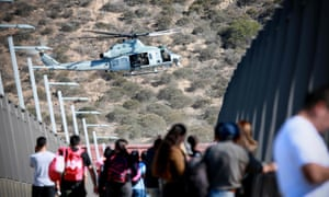 A US military helicopter flies past a pedestrian bridge after the closing of the United States-Mexico border south of San Diego, California.