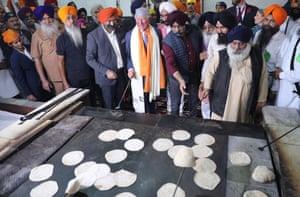 New Delhi, India Charles, Prince of Wales prepares chapati bread during his visit to Gurudwara Bangla Sahib, the holy temple of Sikhs, in New Delhi