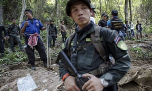 Security forces and rescue workers watching as bodies of trafficked refugees are retrieved from a mass grave in Thailand's southern Songkhla province.