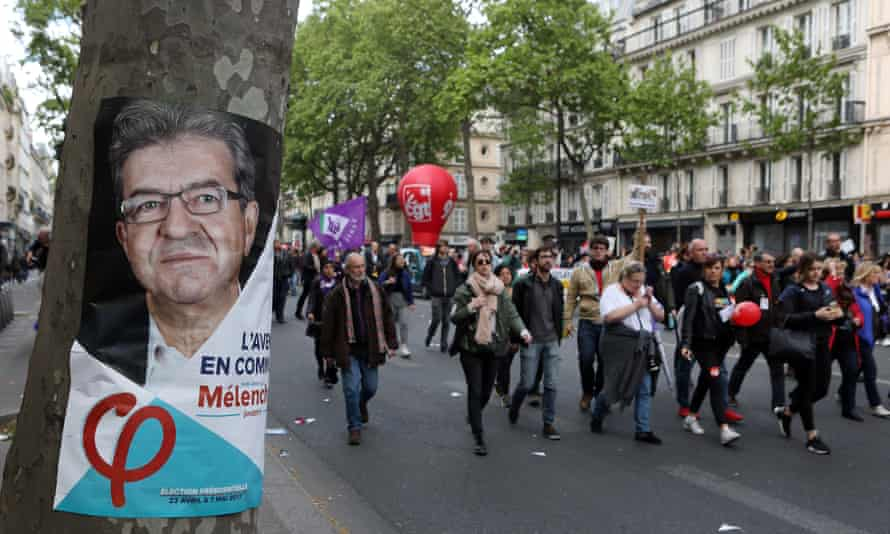 Demonstrators march through Paris on Labour Day last year past a campaign poster for the socialist politician Jean-Luc Mélenchon.