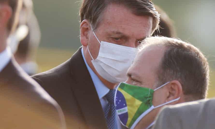 Brazil's president, Jair Bolsonaro, talks with the health minister, Eduardo Pazuello, before a national flag hoisting ceremony