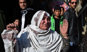 An Afghan woman reacts near the site after a suicide attacker detonated himself at the entrance to a police base in Kabul on 1 February.