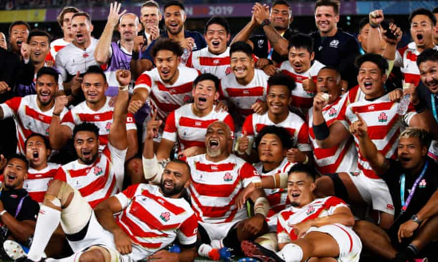 Japan's players celebrating beating Scotland and progressing to the knockout stages.