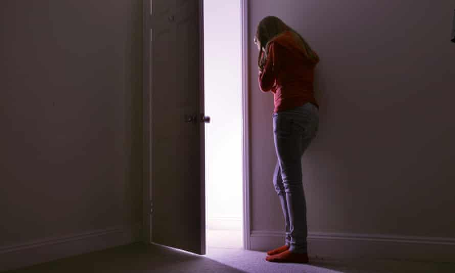 A young woman leans her head against a wall in a dark room