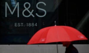 A man carrying an umbrella walks past signage at the head office of Marks & Spencer in London