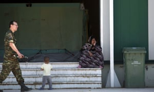 A woman sits on stairs inside a new camp for refugees and migrants set in an abandoned factory in Sindos