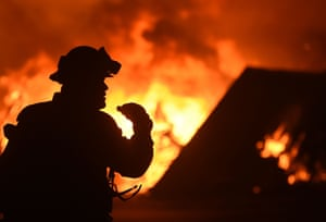 A firefighter drinks water in front of a burning house near Oroville