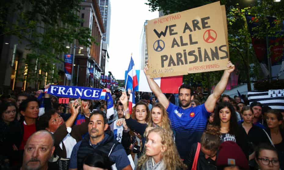 In Sydney, Australia, people hold up placards during a vigil for victims of the 2015 Paris terror attacks.