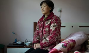 Zheng Ruixia on her daughter's bed where she spends most of her days, at her home in Jiyuan, China.