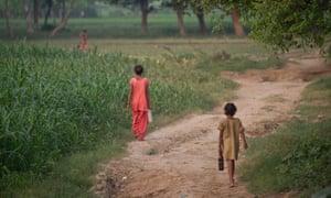 Children walk to defecate in an open field, Uttar Pradesh, India